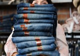 Woman Holding Pile of Jeans