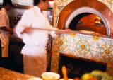 Chef Inserting Pizza Into Wood-Burning Oven